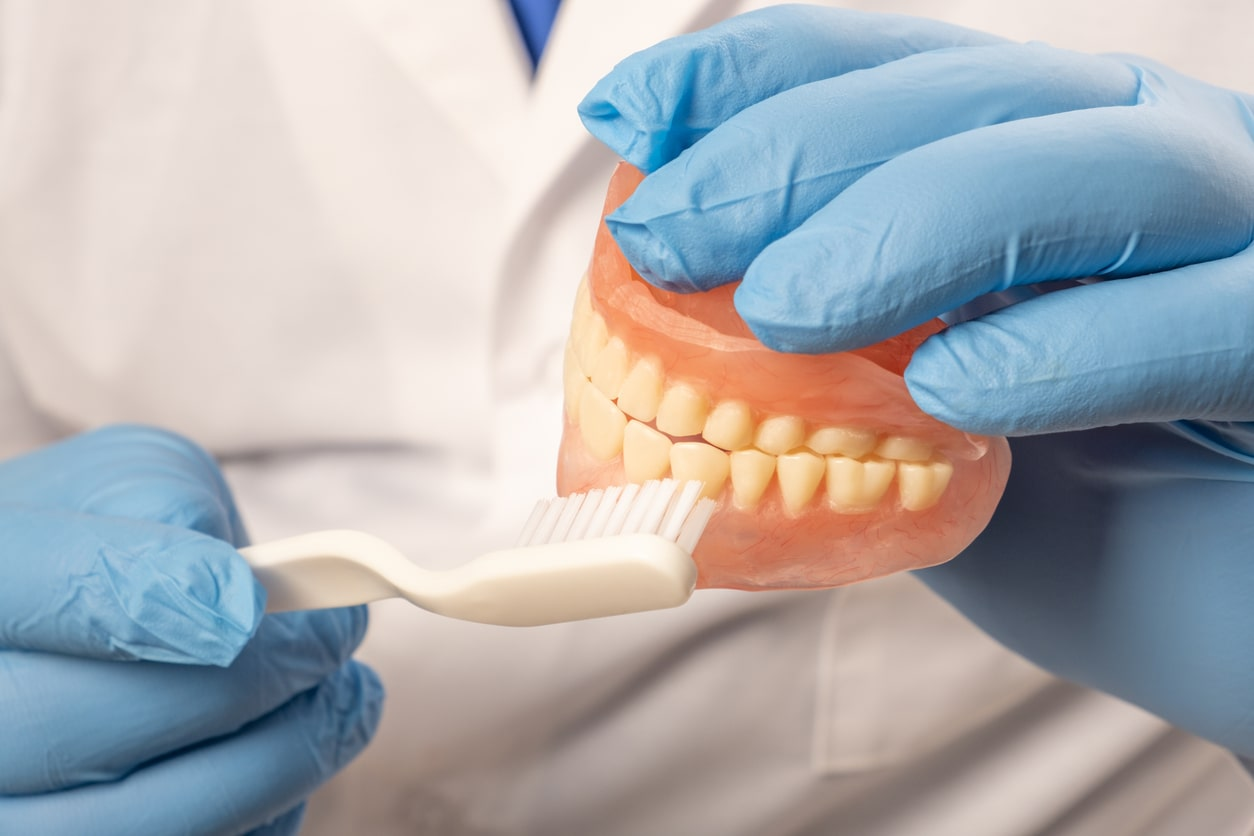 Dentist holding model teeth for gum disease treatment
