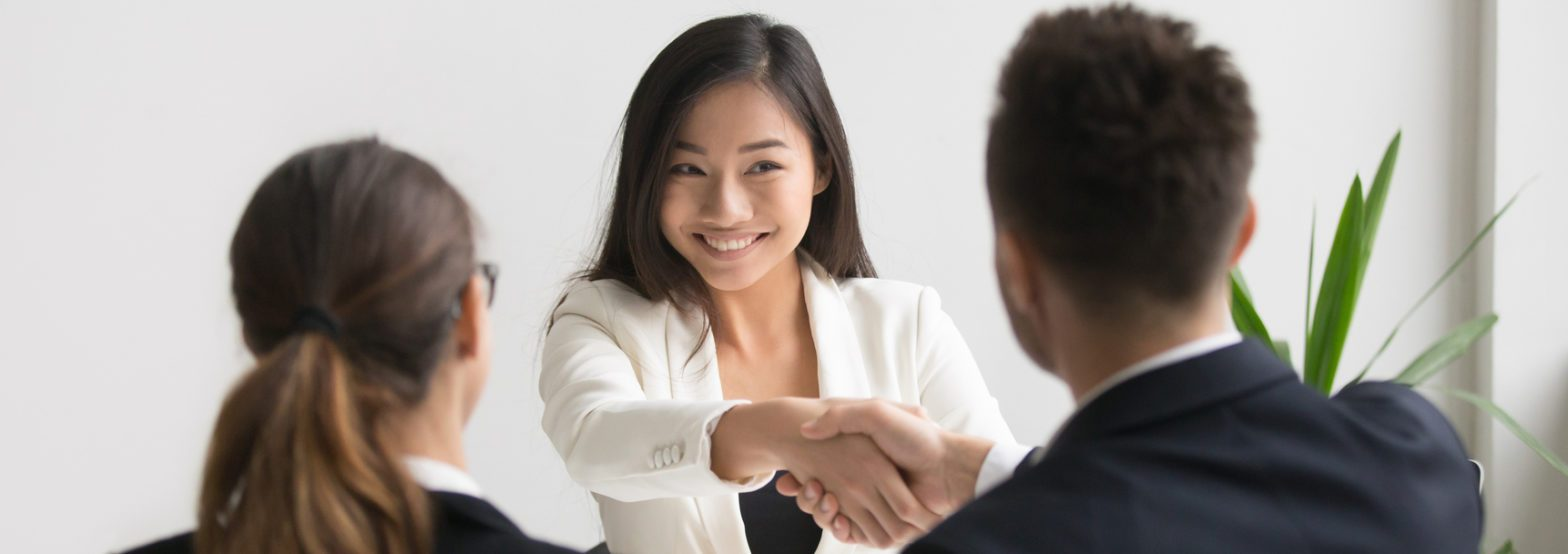 Smiling asian female vacancy candidate shaking hand with hr manager
